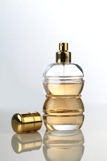 Beautiful Perfume Bottle On White Reflective Surface