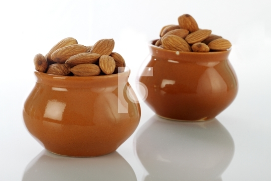 Dry Fruits Almonds in Ceramic Pot on white background
