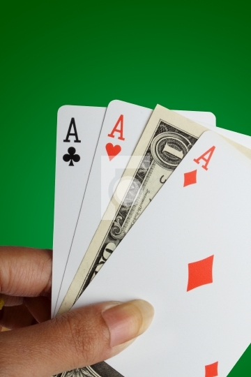 Female hand holding 3 aces and one dollar note