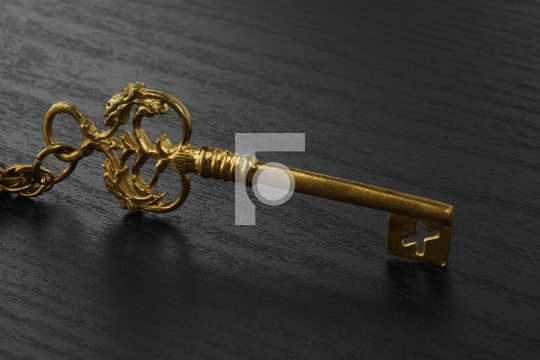 Golden Antique Key on black wooden background