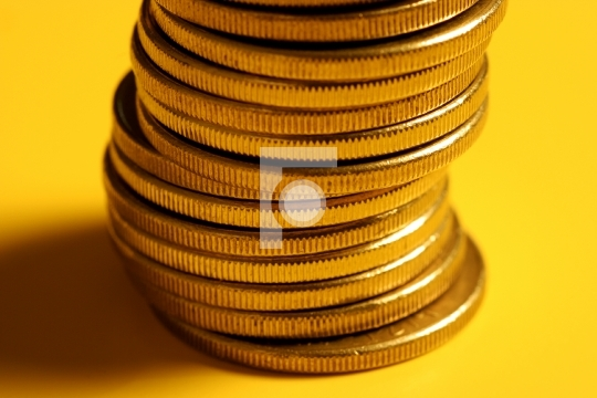 golden coin stacked on yellow background