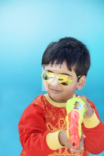 Indian Boy Celebrating Holi with Water Gun - Festival of Colours