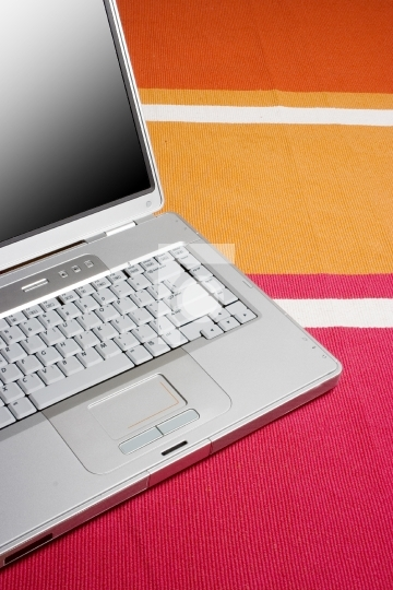 Laptop on a colorful rug, work at home concept