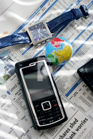 mobile, globe and wrist watch on newspaper