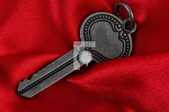 Old vintage key in red satin cloth background