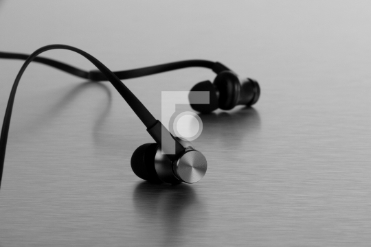 Stylish Black Earphones on Brushed Steel Background