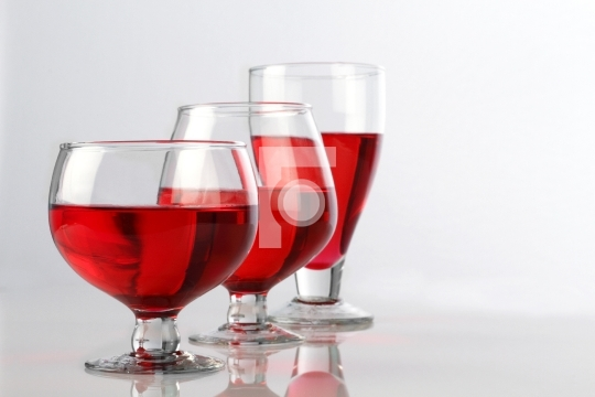 Three Red Wine Glasses on White Reflective Background
