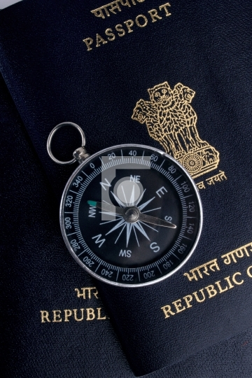 two indian passports and a magnetic compass